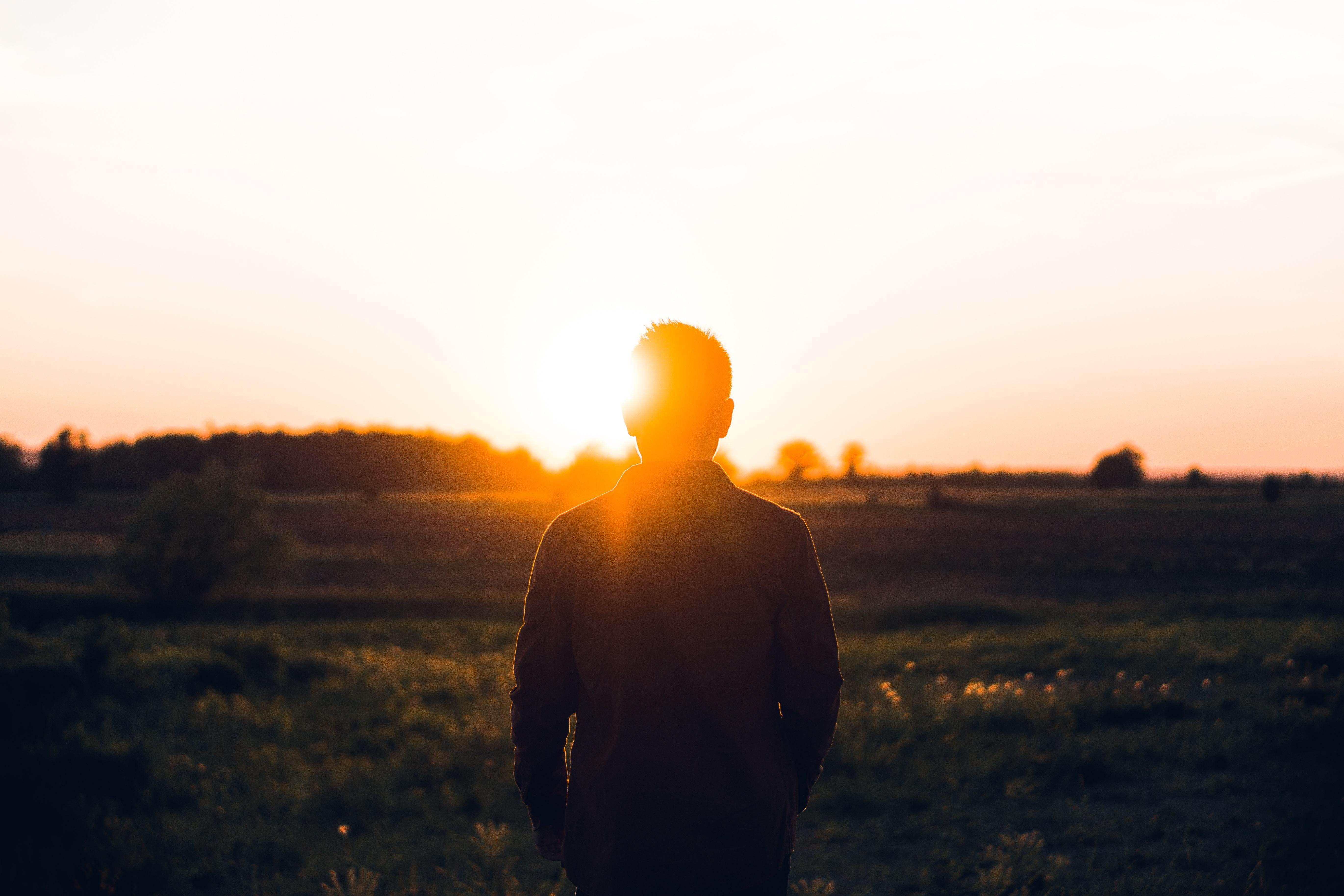 man facing the setting sun