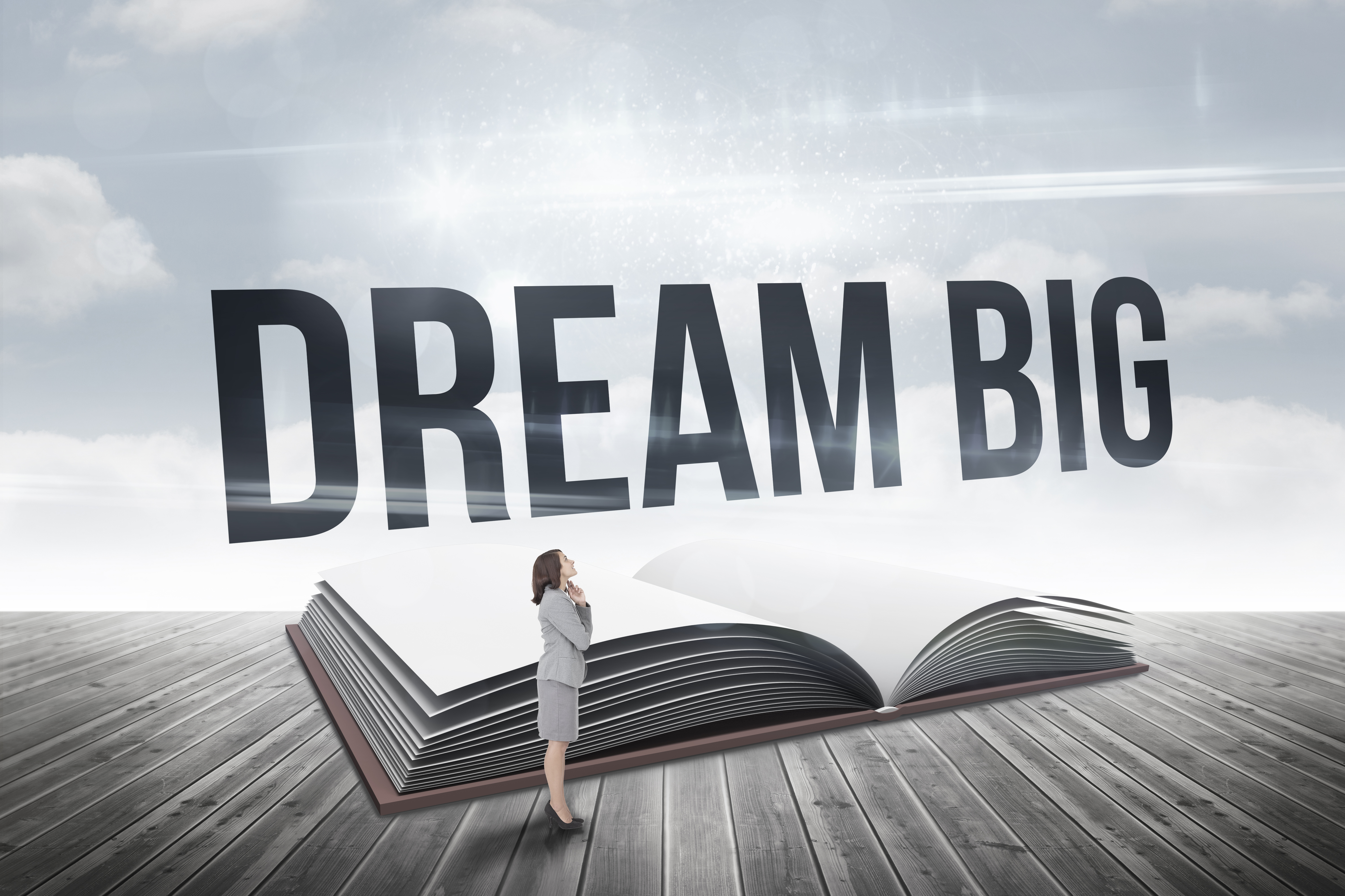 Image of woman standing in front of large book with words dream big
