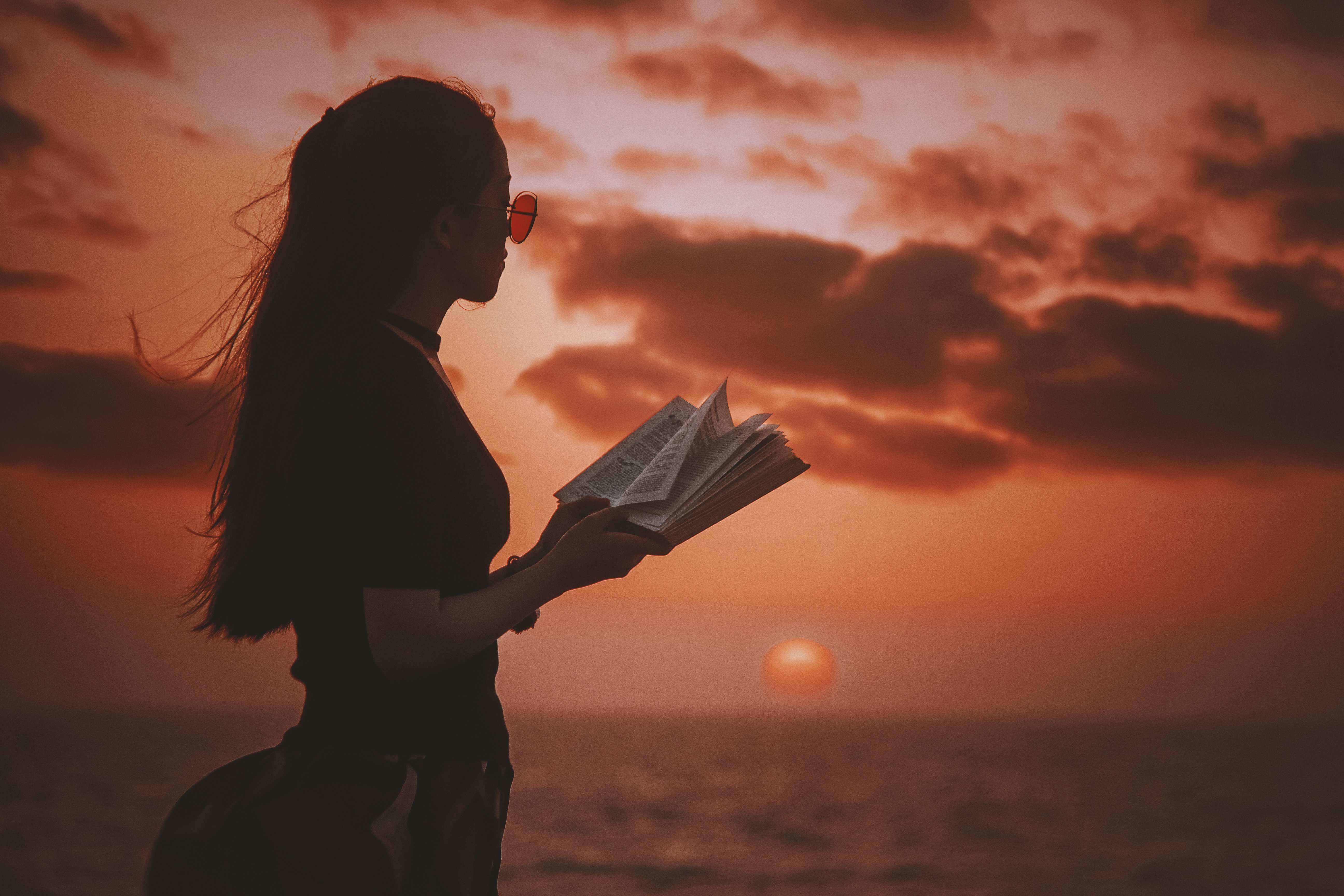 woman with a book at sunset hungry for your book